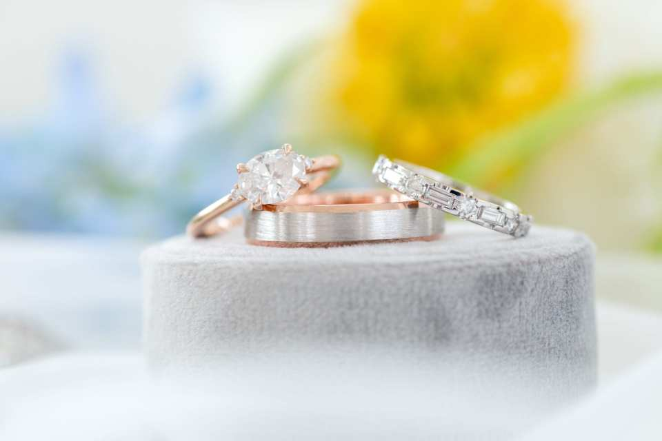 close up of the brides oval diamond engagement ring set in a rose gold band, brides wedding band of emerald and round cut diamonds, grooms wedding band of brushed silver and rose gold