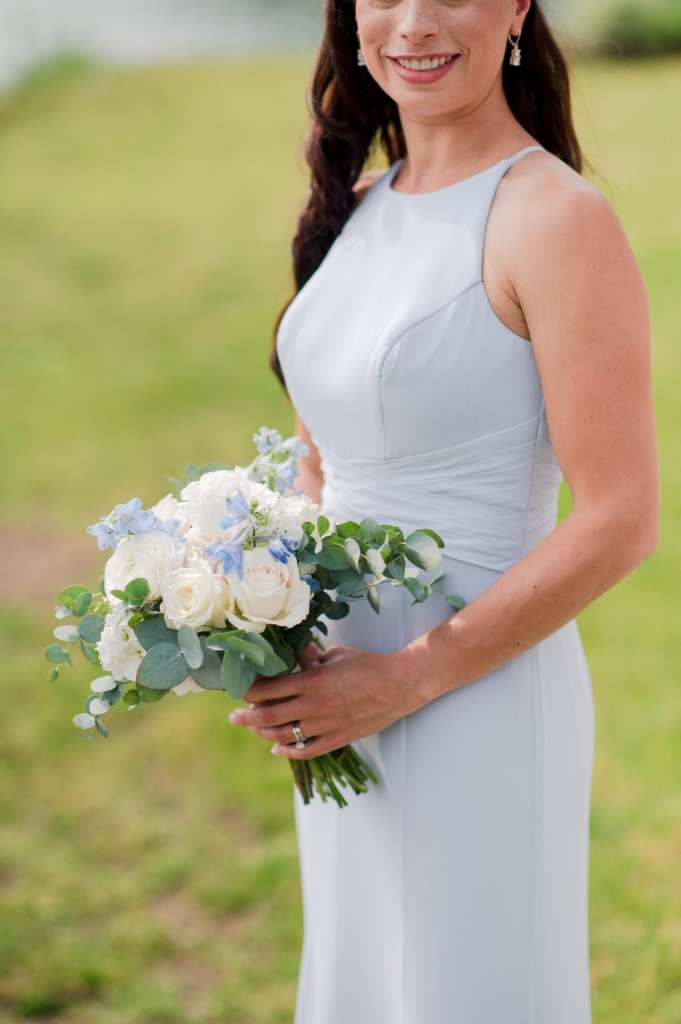member of bridal party in a light blue gown by Watters, holding a handtied bouquet by From Peonies to Paint Chips of white and cream mixed florals, with small blue accent flowers and touches of greens