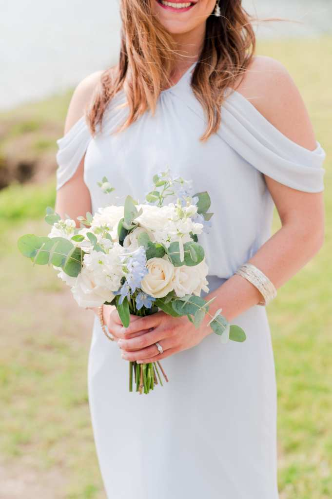member of bridal party in an off the shoulder light blue gown by Watters, holding a handtied bouquet by From Peonies to Paint Chips of white and cream mixed florals, with small blue accent flowers and touches of greens