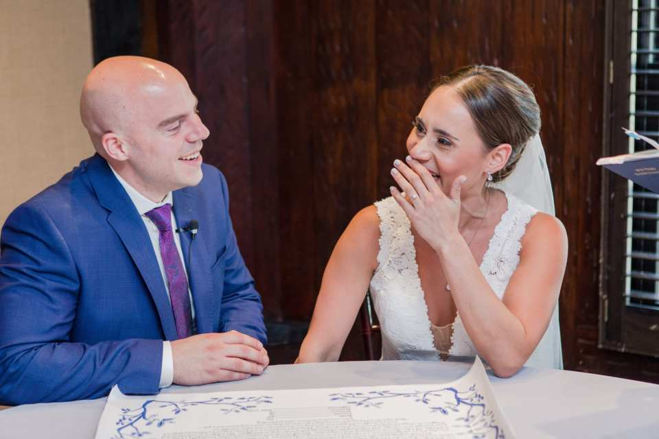 bride and groom giggle during the signing of the Ketubah