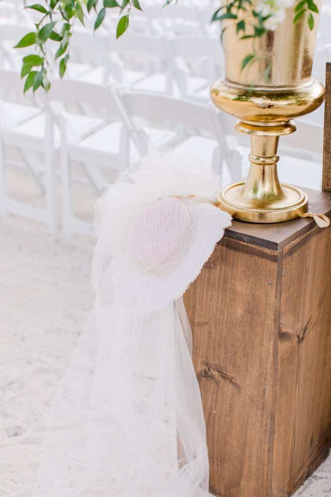 details of the ceremony location: wooden boxes with gold floral urn overflowing with greens