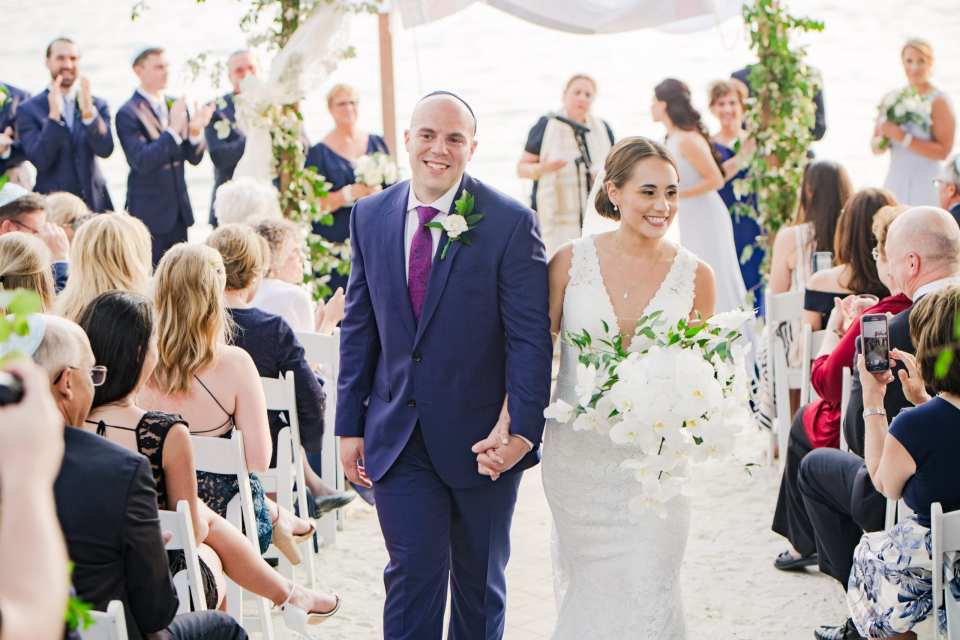 the new mr and mrs walk back down the aisle, smiling