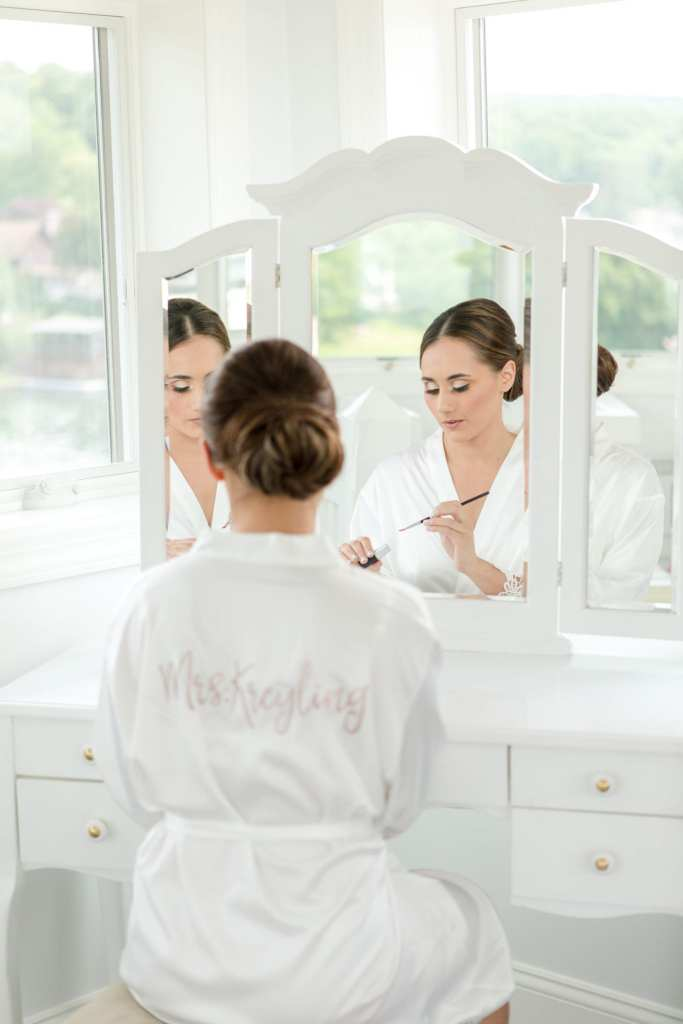 Bride in personalized white robe sitting at makeup table putting on makeup in the mirror