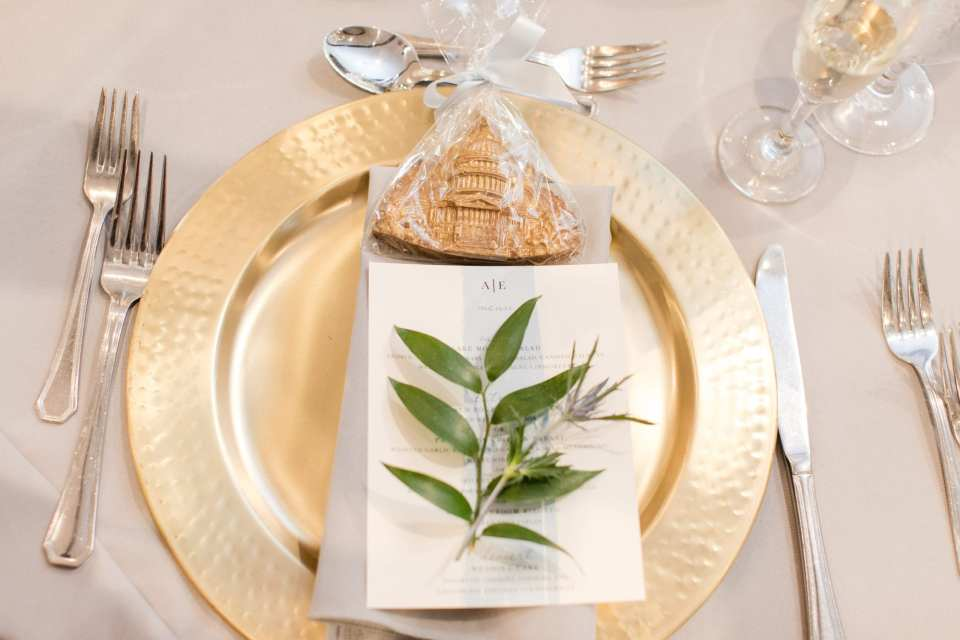 place setting of with menue, floral and cookie favor displayed on gold charger