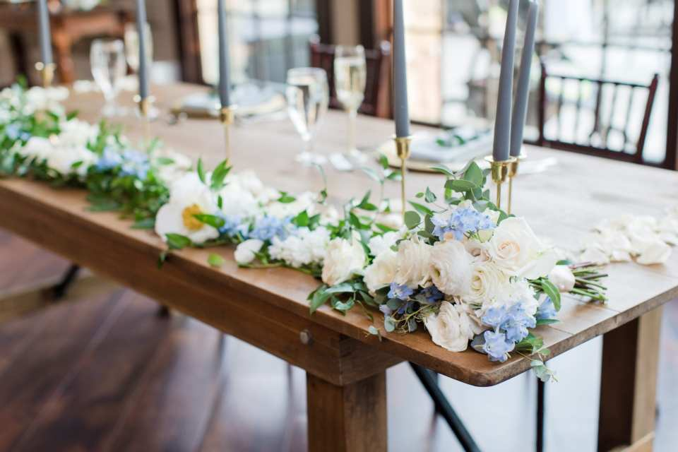close up of the detail on the wooden sweetheart table, focusing on the white floral garland on the table with blue floral accent, along with the blue taper candles in gold candle holders by From Peonies to Paint Chips