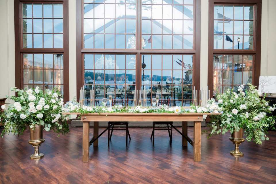 wide angle photo of the wooden sweetheart table in front of expansive windows showing the lake behind the Lake Mohawk Country Club. Florals on top of table, as well as on either side with greens and white roses and peonies, with touches of blues, by From Peonies to Paint Chips