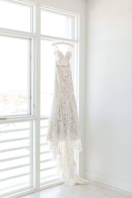 full length photo of the brides lace gown hanging from a white silk hanger in front of sliding doors to a balcony in the bridal suite
