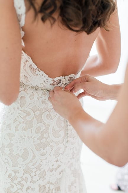 the back of the bride being buttoned into her lace gown