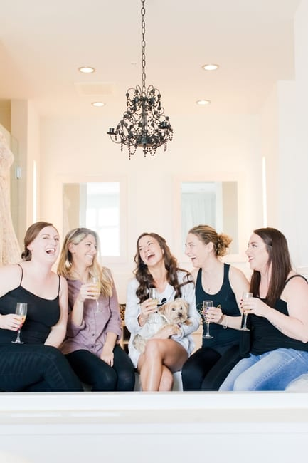 the bride and her friends casually sitting in the bridal suite drinking champagne