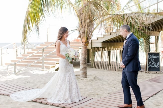 the groom sees his bride for the first time during their first look on the beach. his expression is priceless shock and awe
