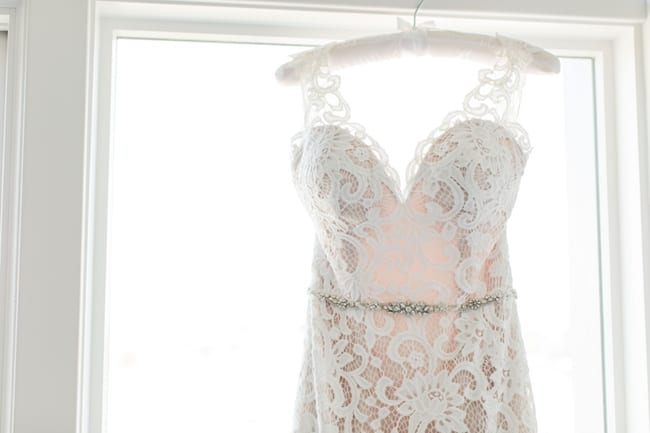 close up photo of the brides lace gown with rhinestone belt hanging on a white silk hanger