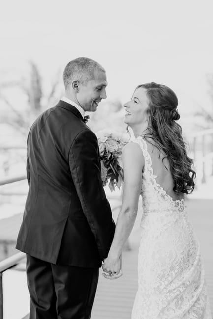black and white photo of the bride and groom laughing at one another while holding hands, photo from behind