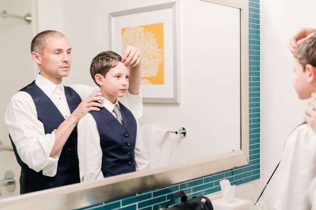 groom and his son in their tuxedo vests and white shirts standing in front of a mirror doing sons hair in preparation for the wedding