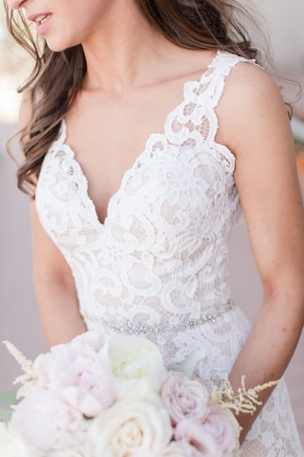 close up of the details of the brides lace gown and rhinestone belt