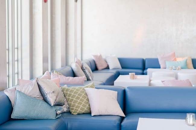 close up of the indoor lounge reception space with blue couches and many pillows in various shades of pink and silver