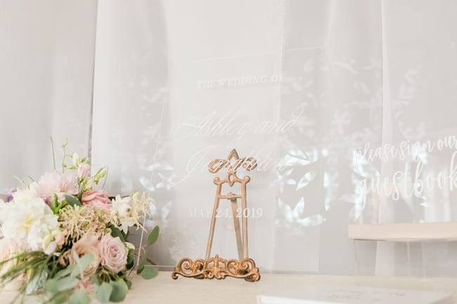 acrylic signage throughout the lounge reception with a small floral piece of blush and white florals with greens
