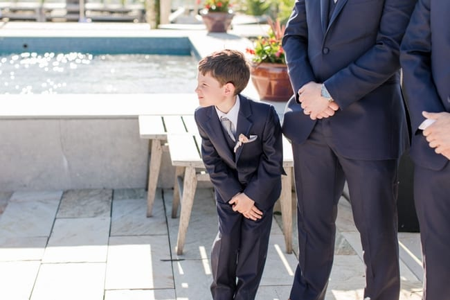 a candid photo of the grooms young son trying to take a peek at the bride as she comes down the aisle