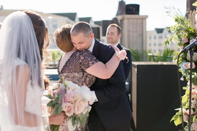 The groom hugs the mother of the bride, who walked her down the aisle