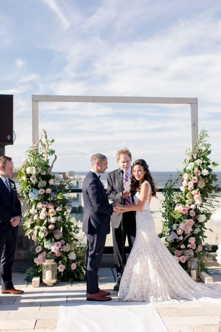 the bride and groom exchange vows overlooking the beach in front of custom floral altar pieces