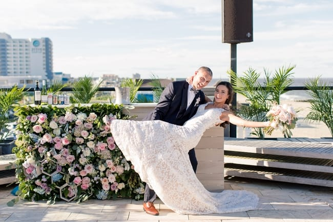 groom dipping his bride in front of custom floral decorated bar outside overlooking the beach