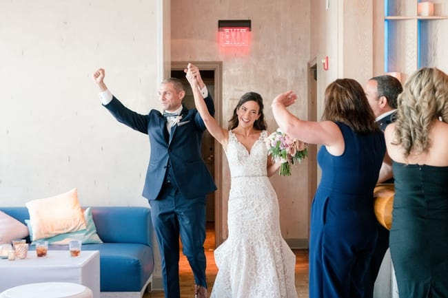 the bride and groom entering the reception as husband and wife, holding their arms in the air