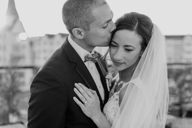 black and white photo of the bride wrapped in her veil, receiving a kiss on her forehead from her groom