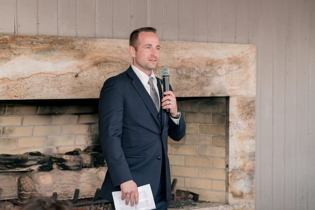 The best man makes his speech in front of a large cream colored brick fireplace