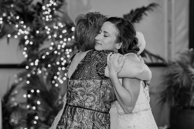 black and white candid photo of the bride and her mother embracing