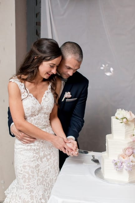 The bride and groom cut their three tier white polygon shaped wedding cake with floral accents of light purple, pink, blush and white roses and peonies