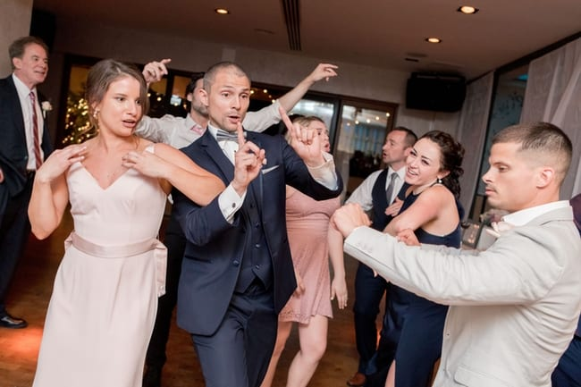 The maid of honor, groom, brother of the bride and other guests dancing during the reception