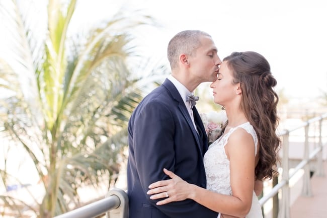 The groom kisses his brides forehead as he is holding her in his arms in front of a palm tree