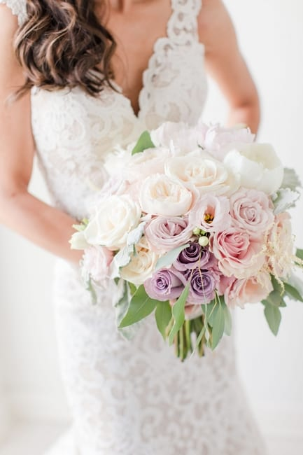 The brides bouquet of light purple, pink, blush and white peonies and roses held at her waist, without her face in view