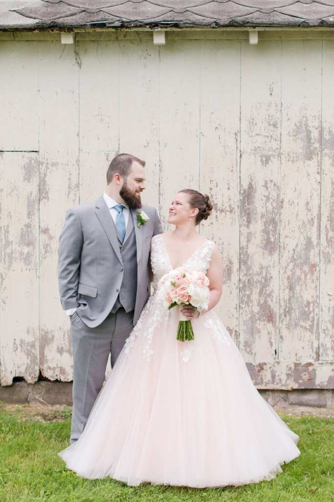bride and groom side by side, each with an arm around the others waist, smiling at each other during the first look outside of a white washed barn