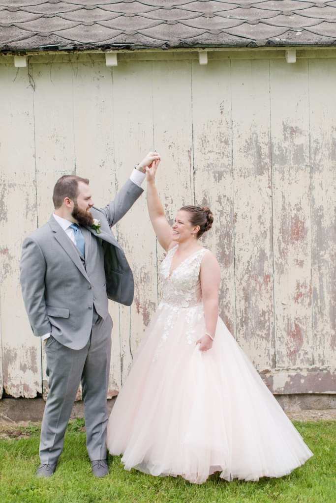 photo of the groom twirling his bride outside of a small barn at the Updike Farmstead