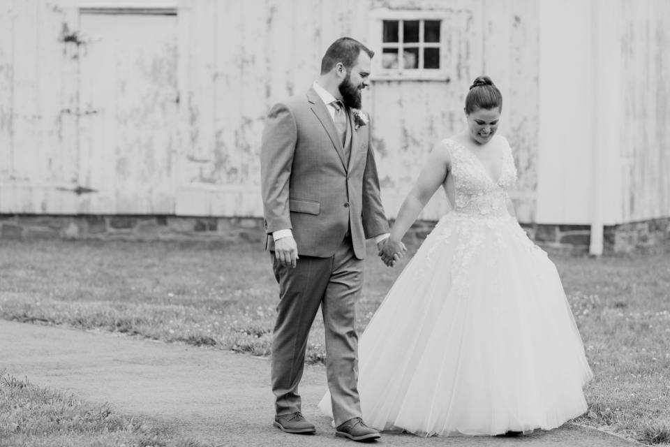 black and white photo of bride and groom walking hand in hand along a path, enjoying one anothers company, at the Updike Farmstead
