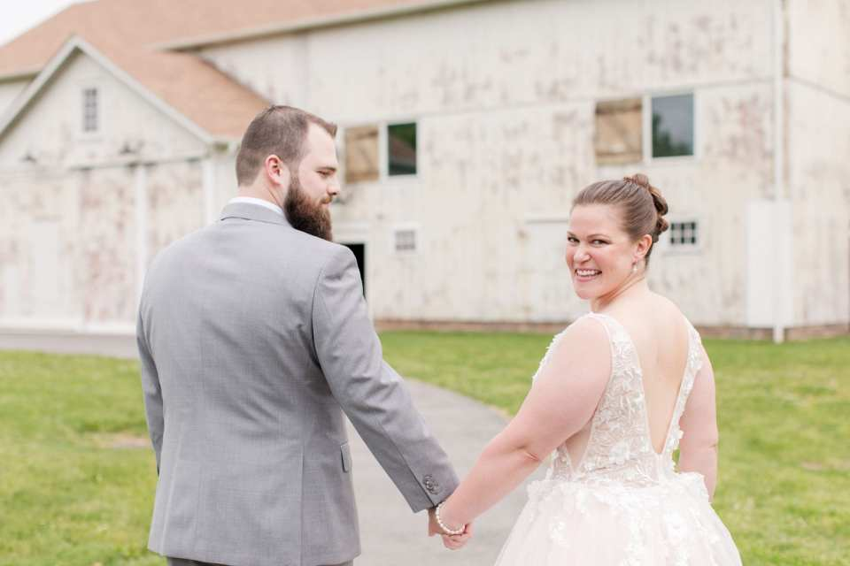 bride and groom walking hand in hand away from camera in front of one of the barns at the Updike Farmstead, with bride looking back smiling at camera