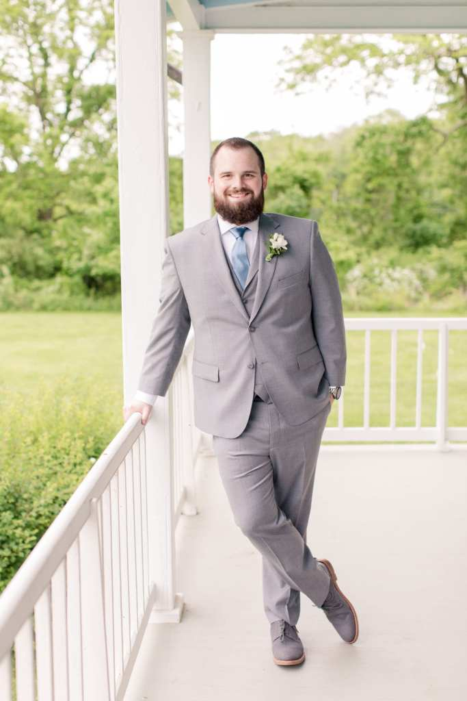 groom posing with one hand on the railing, one hand in his pocket, smiling at the camera while on the porch of the farmhouse of the Updike Farmstead in Princeton, New Jersey
