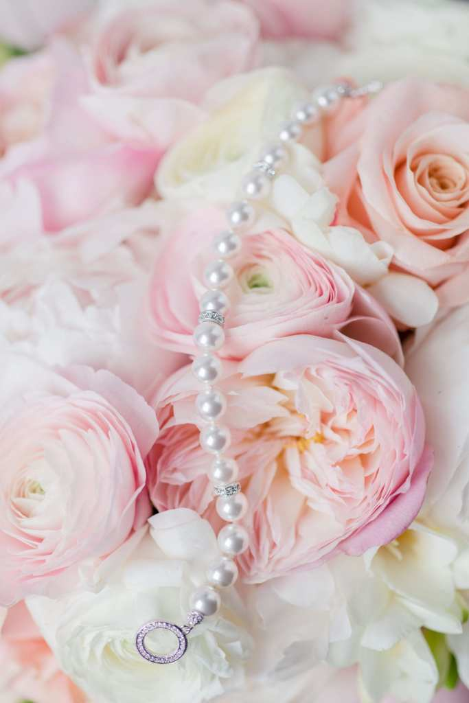 brides pearl bracelet laid out over her bridal bouquet of pink and white florals