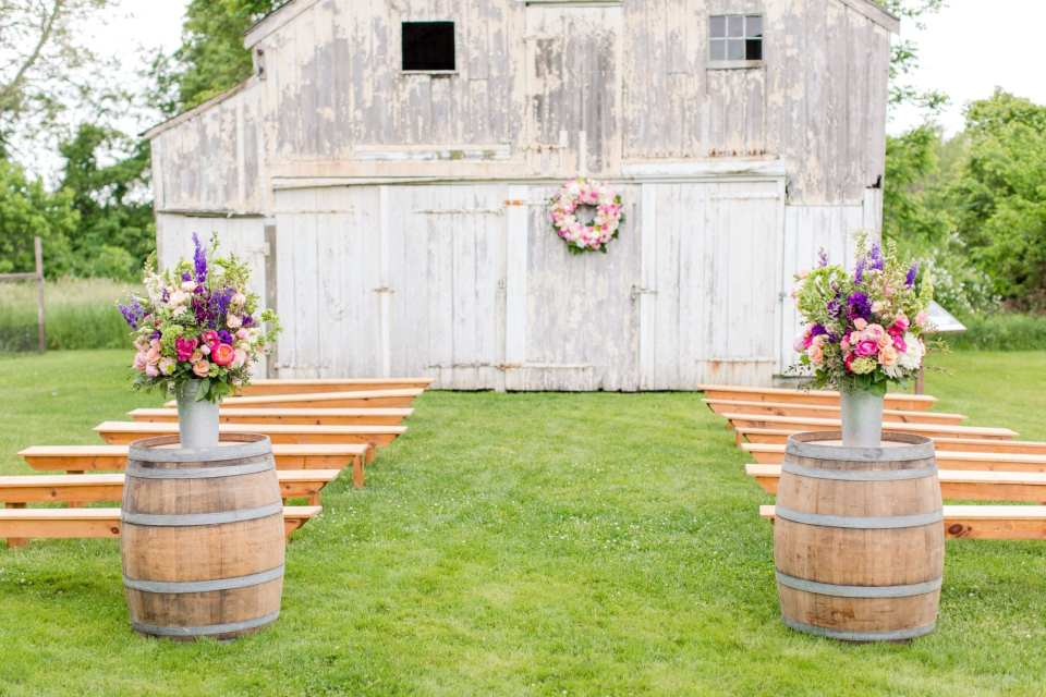 wide angle photo of the White washed barn, guest bench seating, and aisle decor all in image.