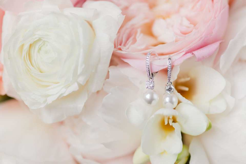 the brides diamond and pearl drop earrings on a light pink peony in her bridal bouquet