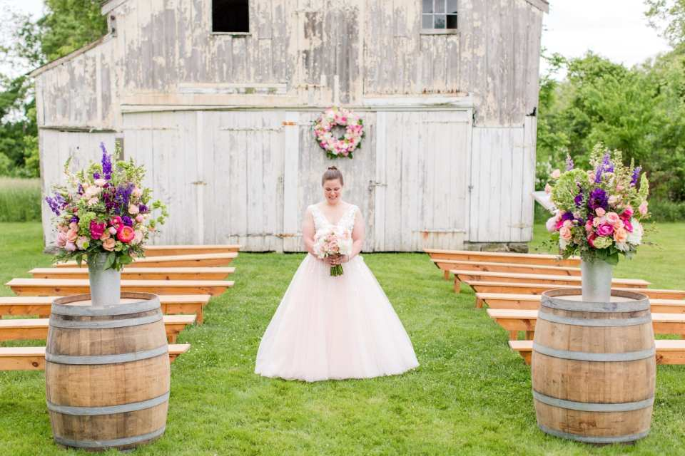 wide angle photo of the bride in pink tulle Jovani gown in the middle of the ceremony location aisle, gazing down at her bridal bouquet by the Flower Shop of Pennington Market. White washed barn, guest bench seating, and aisle decor all in image at the Updike Farmstead