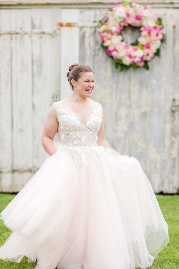 bride in her blush tulle v-neck Jovani wedding gown carrying it with two hands smiling as she looks off into the distance on the farmstead. White washed barn with floral wreath in the distance behind her