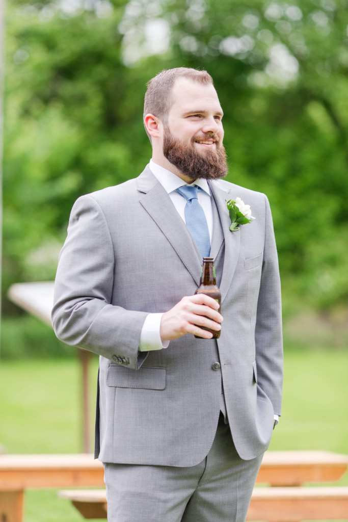 3/4 photo of groom in grey three piece suit looking off into the distance, holding a bottle of beer in his hand, smiling.