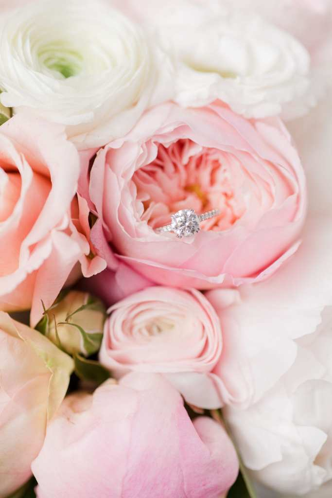 brides round diamond engagement ring with diamond band in the center of a pink peony in her bridal bouquet