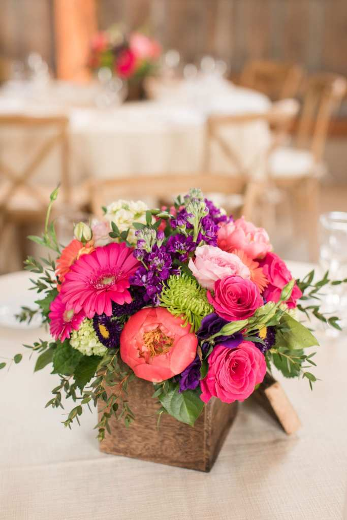 close up of small reception floral arrangement of multicolored wildflowers, roses, peonies in a small wooden box by the Flower Shop of Pennington Market