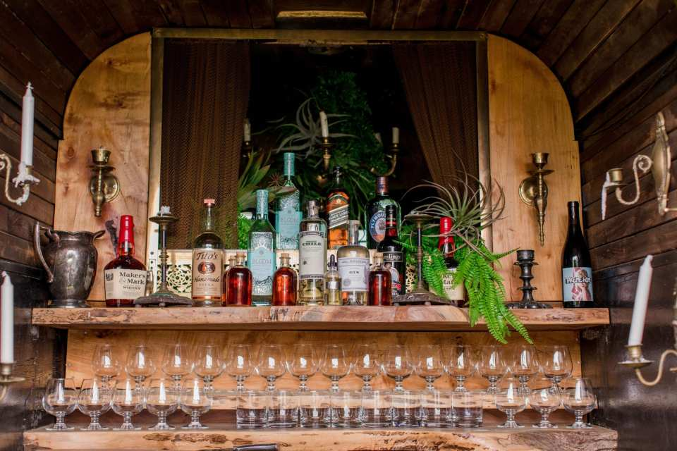 details inside the 13th Street Cocktails converted horse trailer into barn. Eloquent display of liquors, candles, candle sconces and glassware