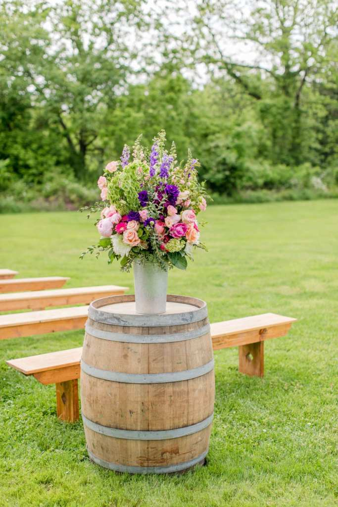 details of the wedding ceremony: one of two wine barrels at the start of the aisle at the ceremony location with floral display in various shades of colors and types of florals by the Flower Shop of Pennington Market