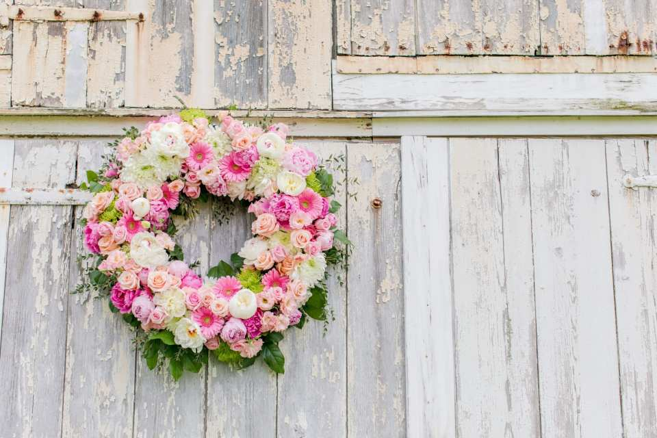 details of the wedding ceremony: the large pink, blush, magenta and cream floral wreath by the Flower Shop of Pennington Market hanging on the white washed barn at the ceremony location