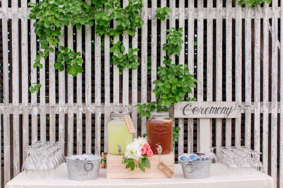 details from the ceremony: beverage station set up of iced tea and lemonade, along with water goblets and sunglasses for guests