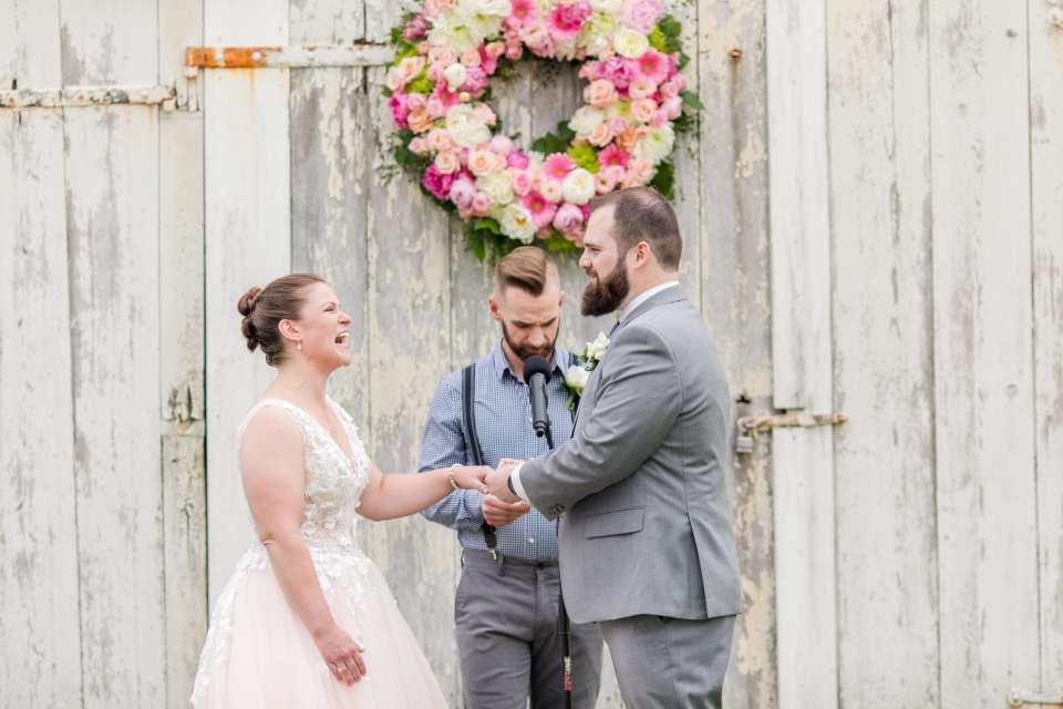 bride laughing during wedding ceremony in front of white washed barn with pink, blush, magenta and cream floral wreath